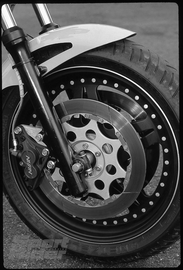 Some glossy black paint improves the look of the leading-axle fork; bolting on some Nissin calipers and an Astralite wheel reduces unsprung mass and improves performance.