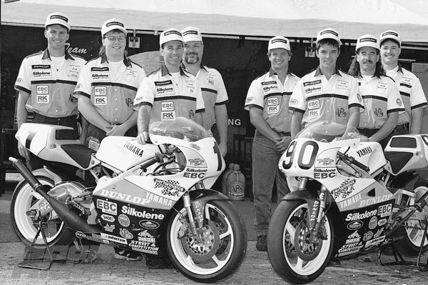 Rich Oliver and teammate Chuck Sorensen (90) stand behind their TZ250 Yamahas surrounded by the Performance South crew. Oliver owns and operates Performance South, and has led the team to the top two